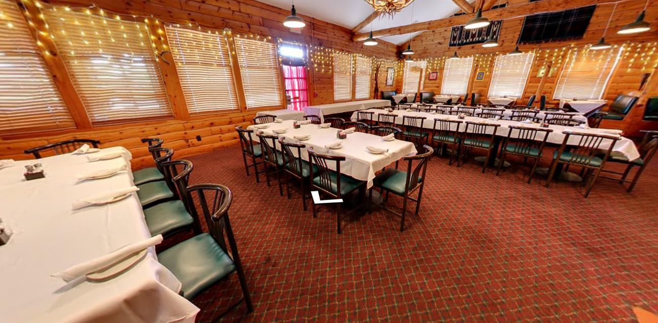 large banquet room with tables covered in cloths with menus and silverware