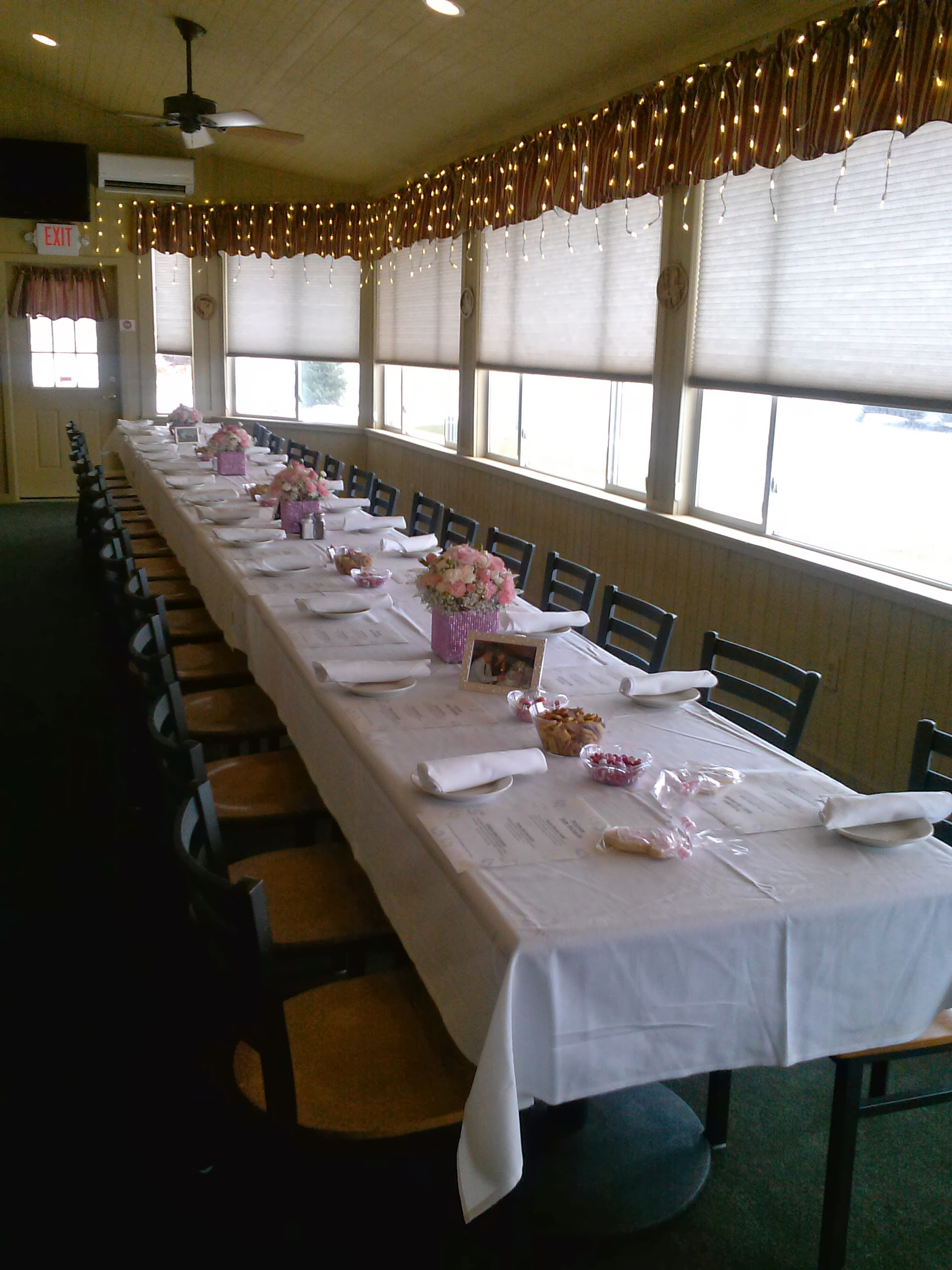 long table with a cloth and silverware with bouquets in the middle