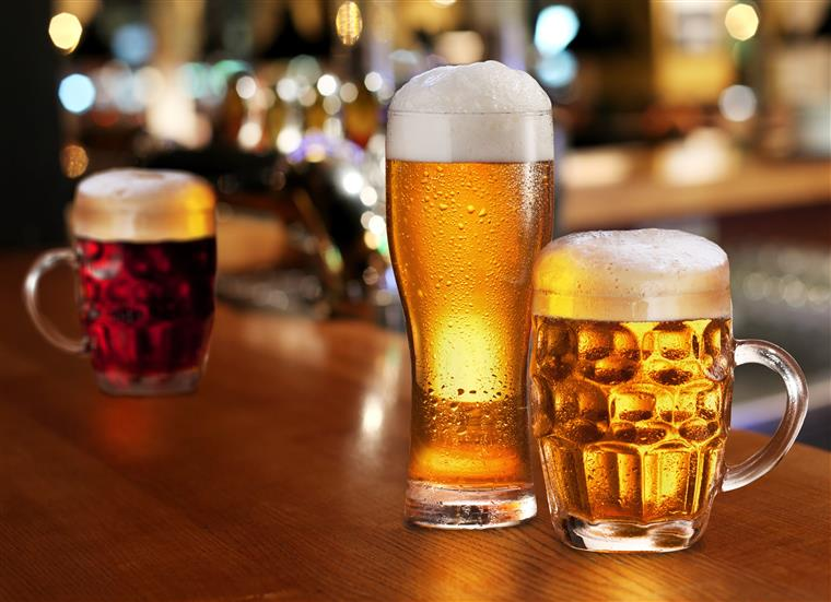 Three full beer glasses on wood bartop, background is blurred