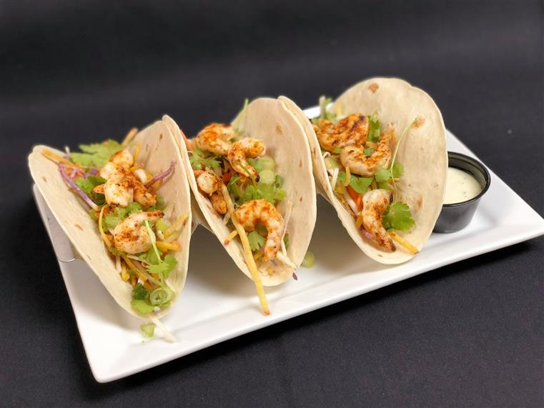 3 shrimp tacos on a plate with dipping sauce