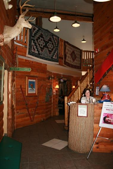 Aspen Restaurant interior. Woman at front counter. Room is decorated with hanging rugs and taxidermy.