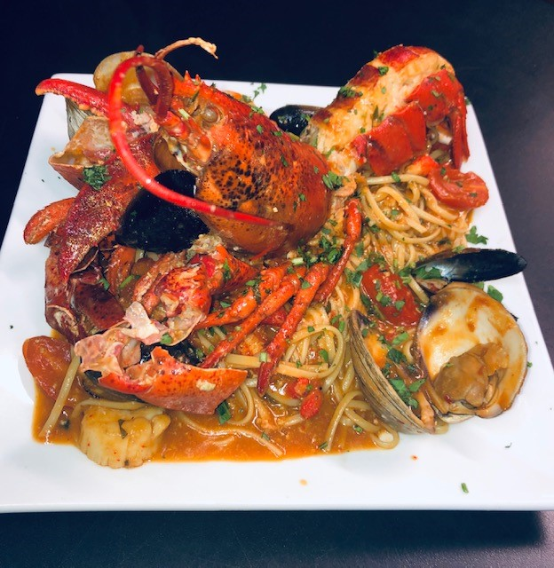 seafood entree with clams, mussels, shrimp and tomatoes around a whole lobster
