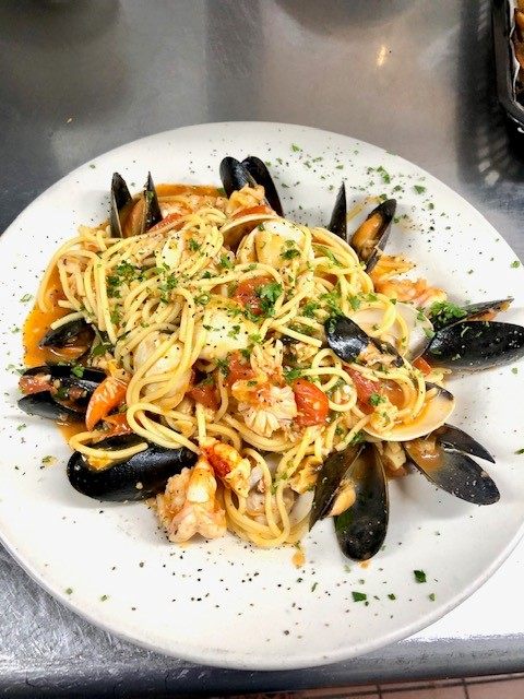 spaghetti with shrimp, mussels, clams, scallops and tomatoes with parsley as a garnish