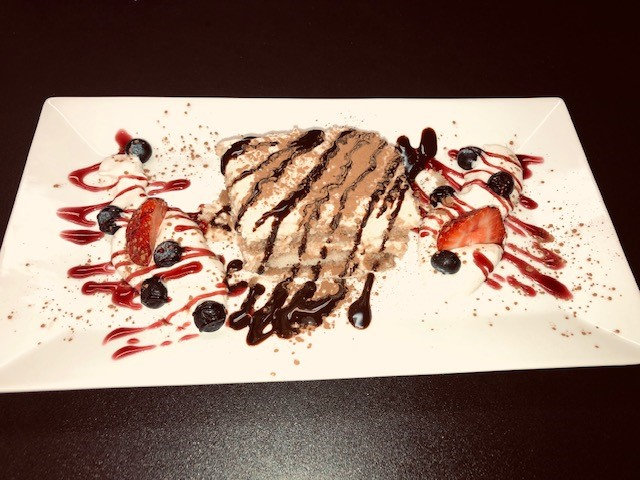 tres leches cake with strawberry and chocolate drizzle served with fresh blue berries and strawberries