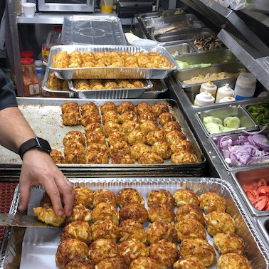 trays of food being prepared for a big to go order