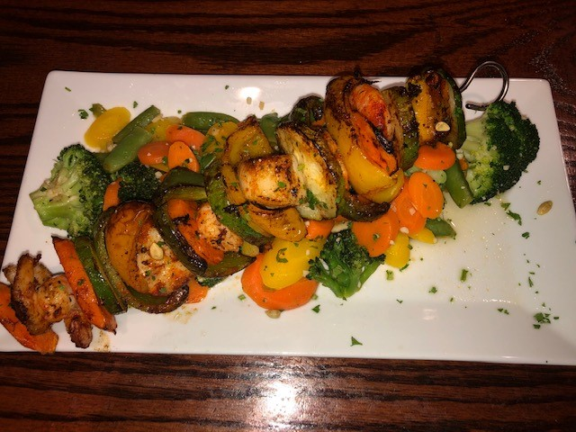 shrimp and vegetable kabobs on a bed of more vegetables