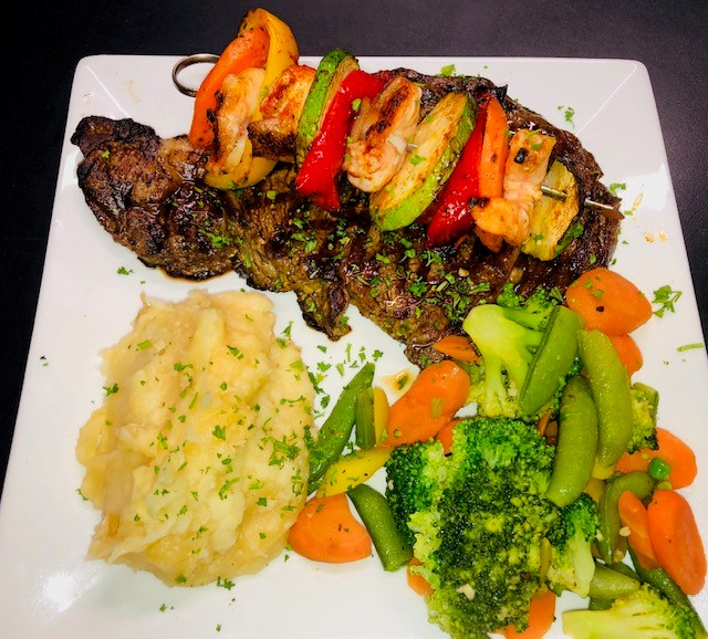 grilled flank steak with vegetable kabobs with mashed potatoes and steamed veggies on the side