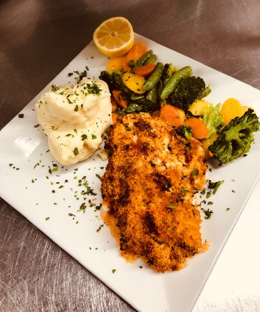 breaded fried fish with sauteed vegetables and mashed potatoes
