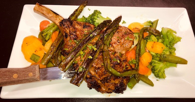 pork chop on a bed of roasted vegetables with grilled asparagus on top