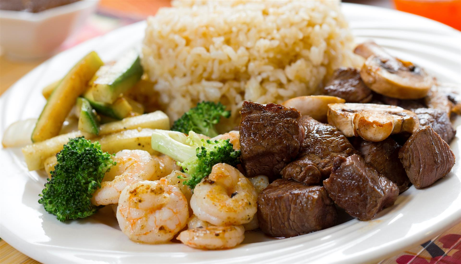 cooked beef and shrimp with a side of vegetables and rice