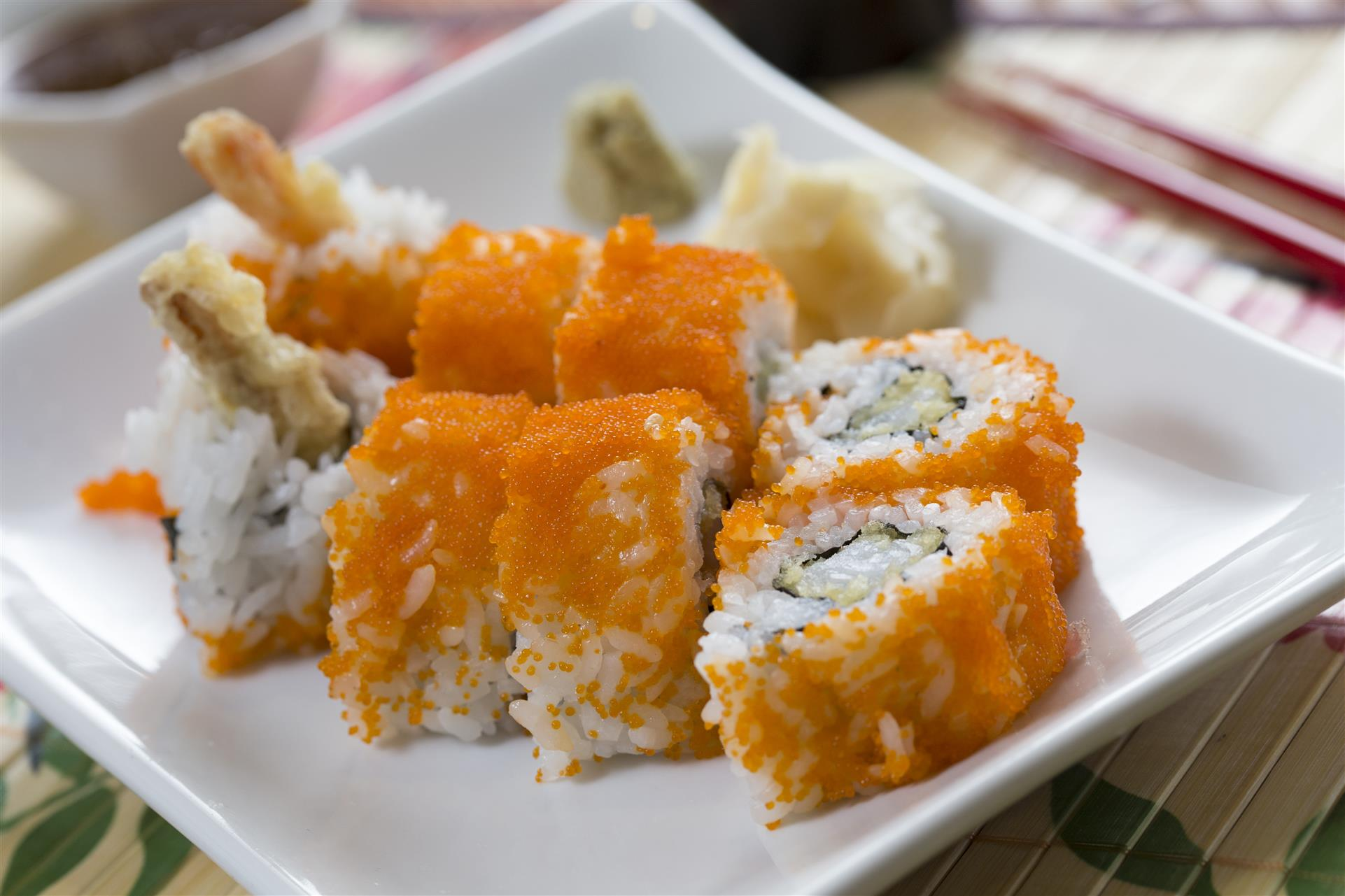 sushi roll with masago on the outside and a side of ginger