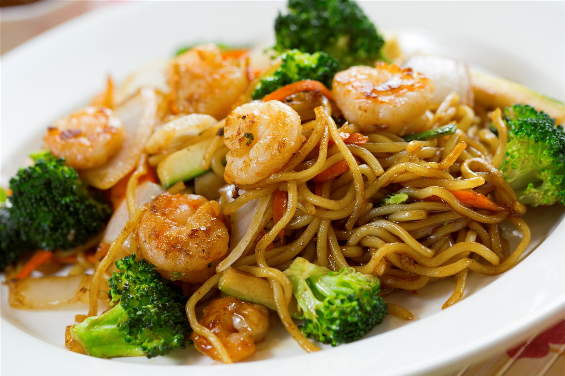 shrimp lo mein with vegetables on a plate