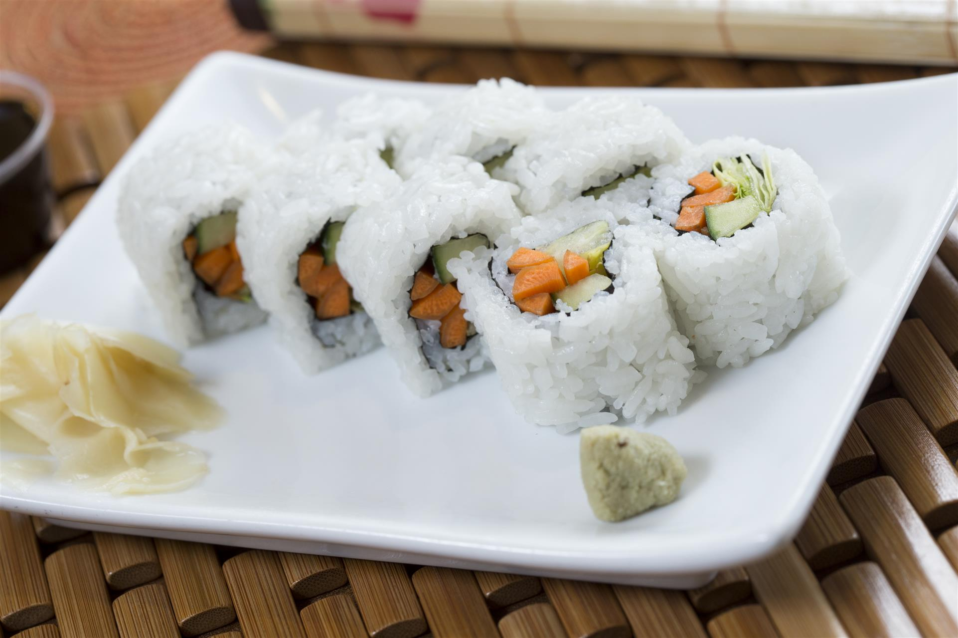 sushi roll on a plate with carrots and cucumbers with a side of ginger and wasabi