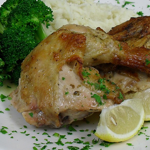 chicken with broccoli, mashed potatoes and a lemon wedge