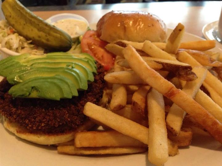 hamburger topped with avocado slices, tomao slice and a side of french fries and a pickle spear