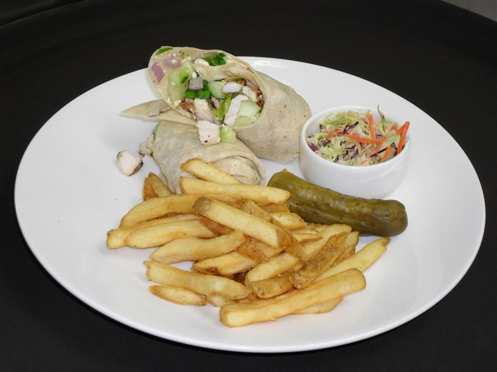 wrap with a variety of ingredients with a side of french fries, pickle spear and cole slaw