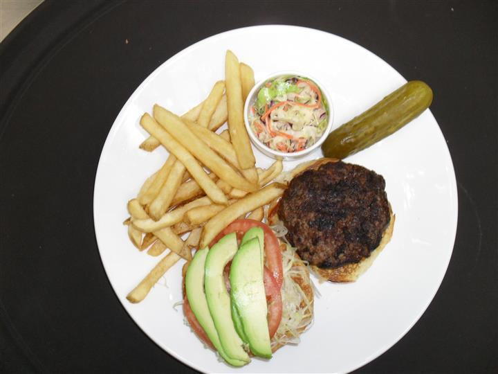 hamburger open faced with shredded lettuce, tomato slices and avocado slices with a side of french fries, pickle spear and cole slaw