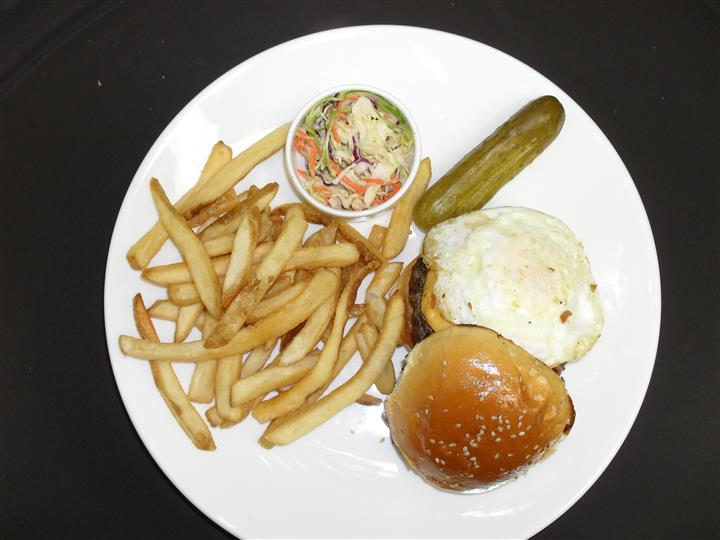 hamburger with cheese, fried egg and a side of french fries, pickle spears and cole slaw