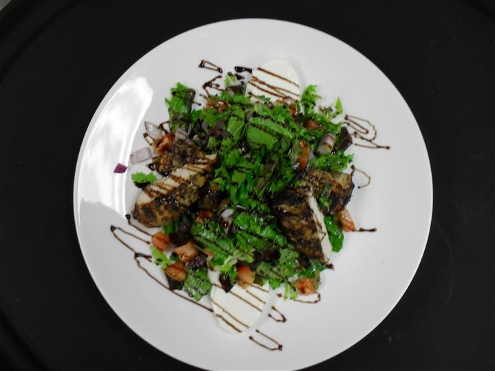 mixed greens with a variety of ingredients and a balsamic drizzle
