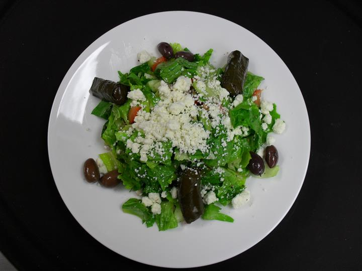 chopped romaine lettuce • tomatoes • kalamata olives • peppers • cucumber • red onion • stuffed grape leaves • feta cheese • house dressing