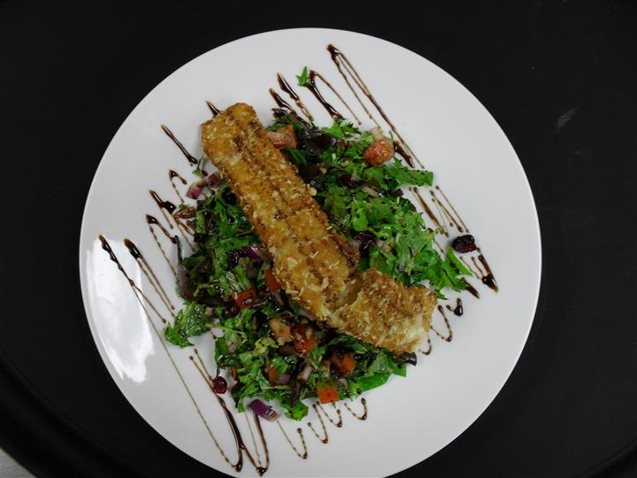 salad with mixed greens and a variety of vegetables topped with salmon