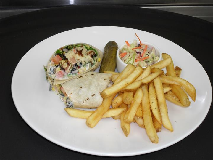 wrap with a variety of ingredients, a side of french fries, cole slaw and a pickle spear