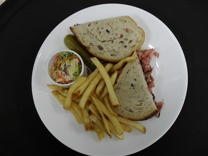 sandwich with roast beef and a side of french fries and cole slaw and pickle spear