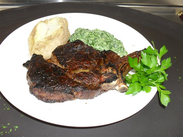cooked steak with a side of creamed spinach and baked potato