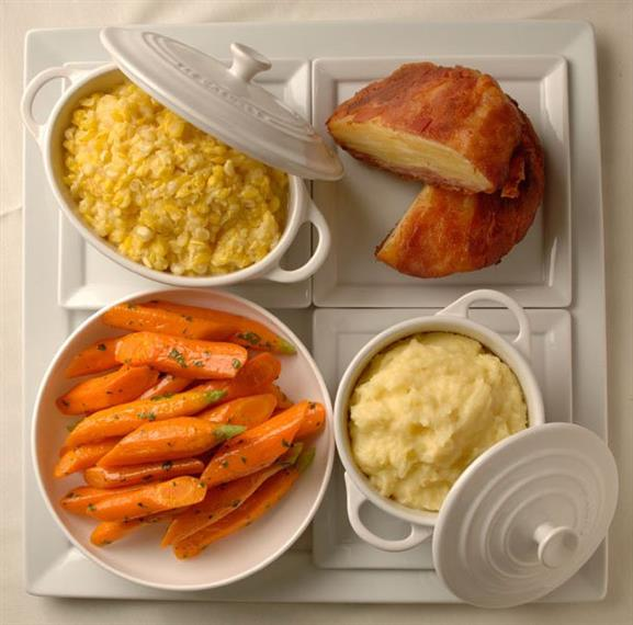 A four dish plate, containing glazed carrots, mashed potatoes, pudding and scrambled eggs
