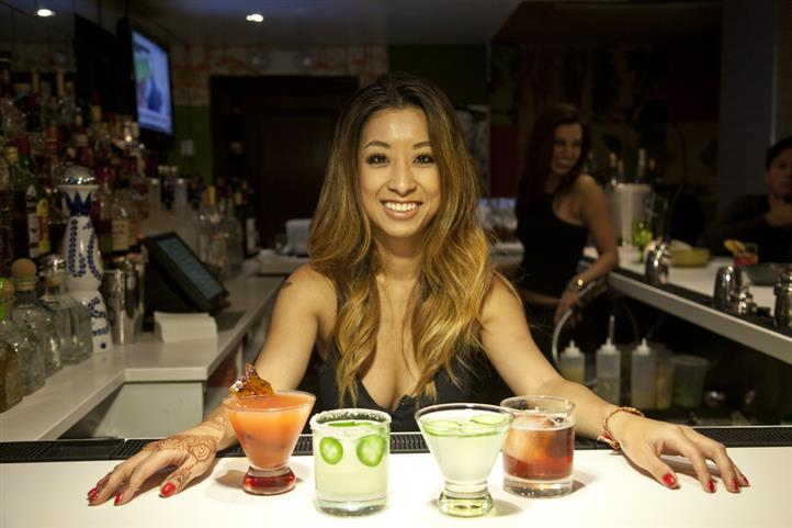 Photo of a smiling bartendress behind the bar, in front of four cocktails