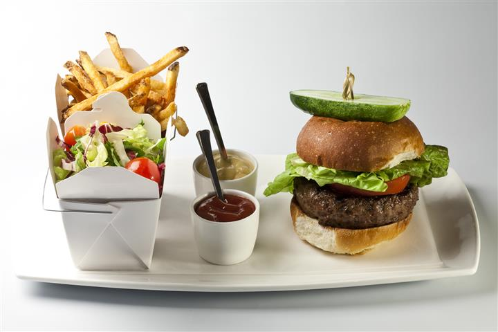 A dish of burger served with French fries, side salad and two dippiing sauces