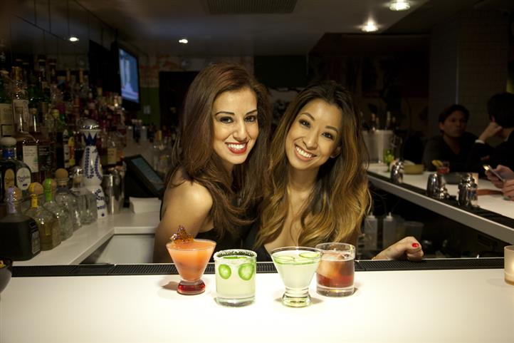 Two smilling bartendresses behind the bar having four cocktails in frond of them