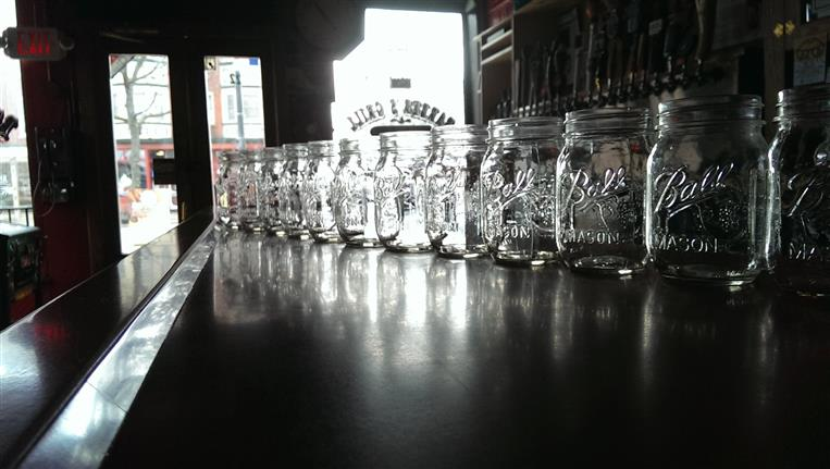 Empty mason jars lined up on bartop.