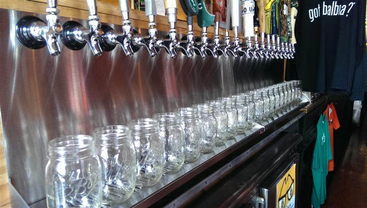 Many mason jars under beer taps