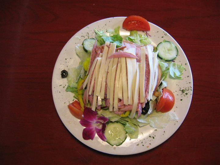 salad topped with slices of cheese and ham