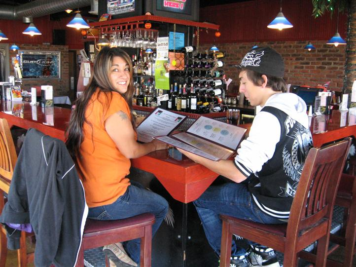 two cutomers sitting at the bar looking at a menu