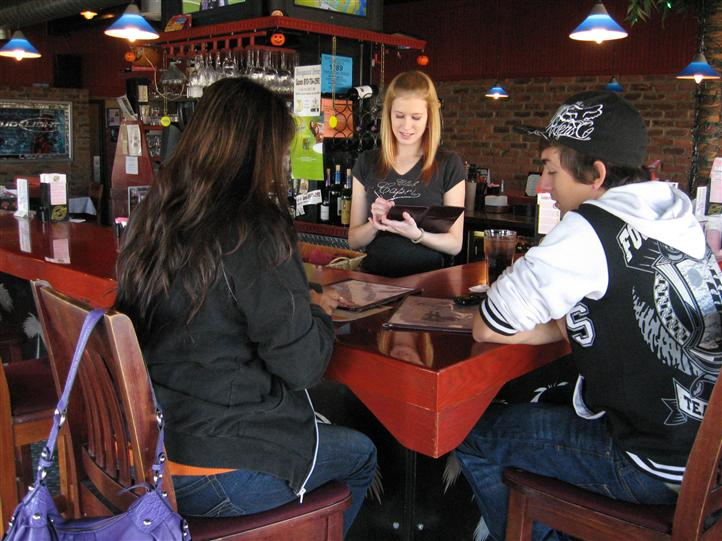 two people sitting at the bar with a waitress taking their order