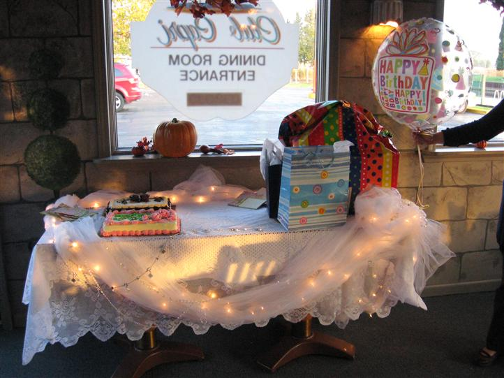 table decorated for a birthday party with a birthday cake and balloon