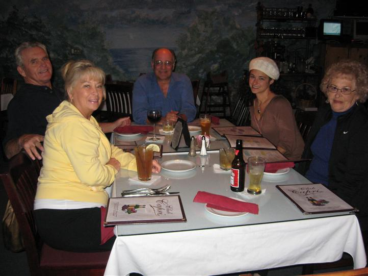 three people sitting at a table smiling for picture