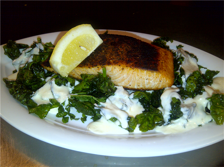 grilled salmon over pasta noodles with a lemon wedge