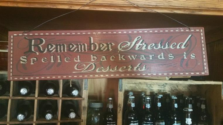 "a sign above a wine rack that reads, ""Remember, Stressed spelled backwards is Desserts"""