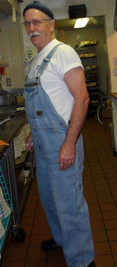 an employee in the kitchen wearing overalls