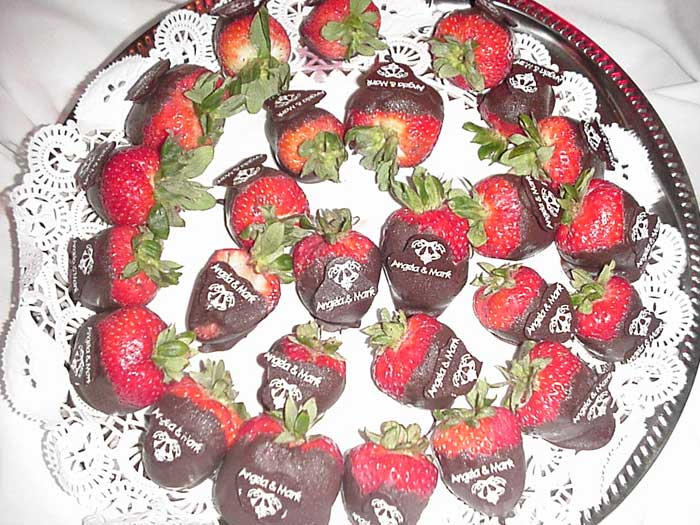 "several chocolate-covered strawberries on a dish, with ""Angela & Mark"" written on each one in white chocolate"