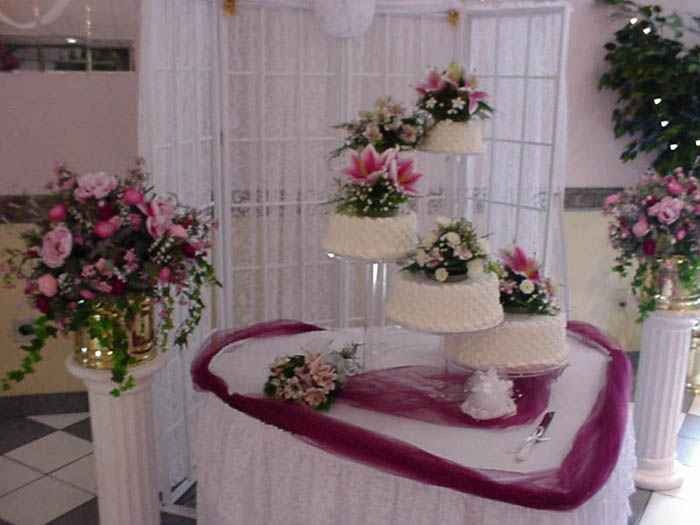 several wedding cakes with floral garnish