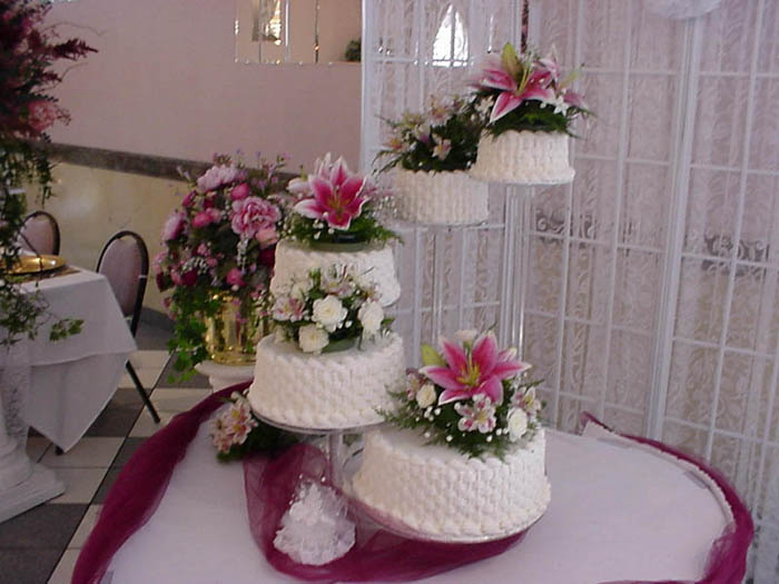 a table with several floral-decorated wedding cakes
