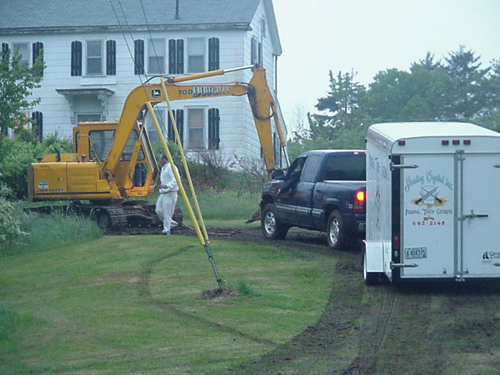 a truck with an  attatched trailer, next to an excavator truck
