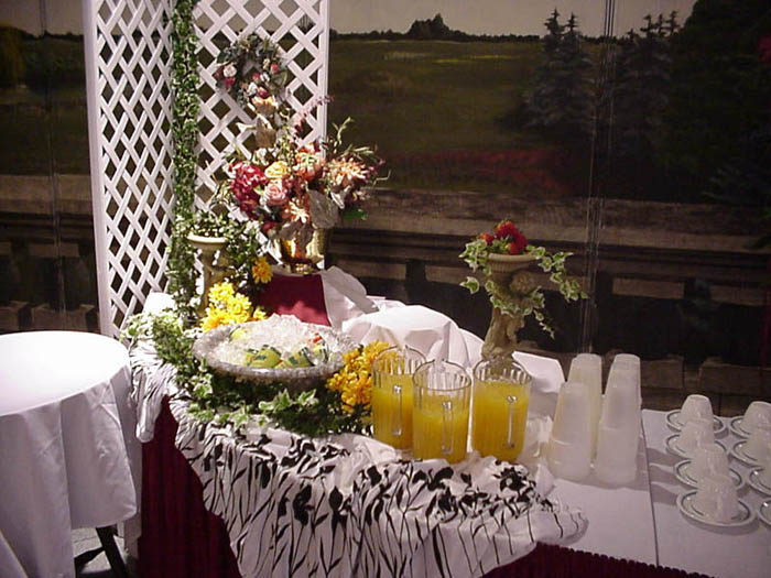 a drink table with cups and pitchers of juice