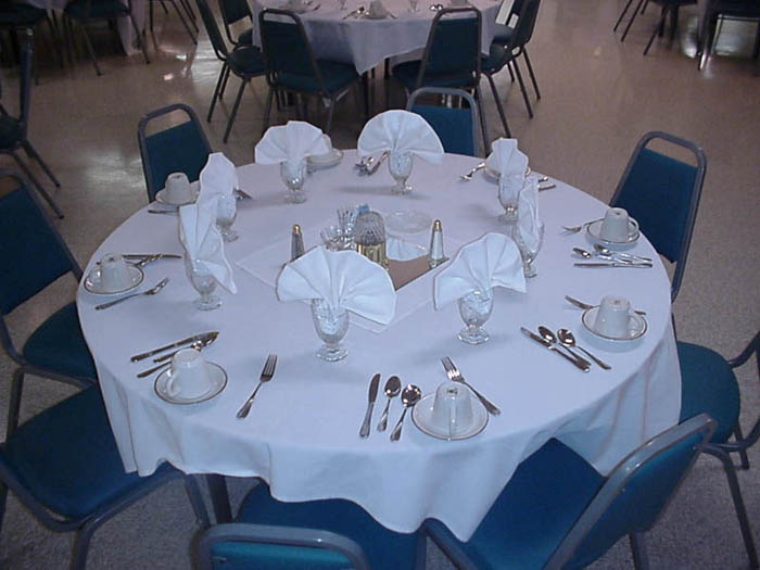 a table set with eating utensils and glasses with fancy folded napkins