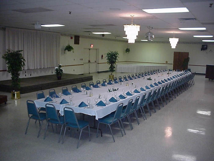 one very long rectangular table with several chairs