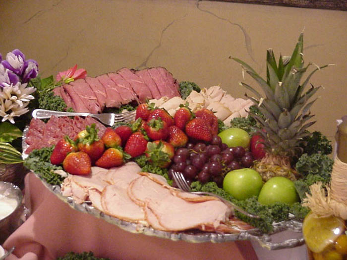 a plate with assorted fruits and cold meats